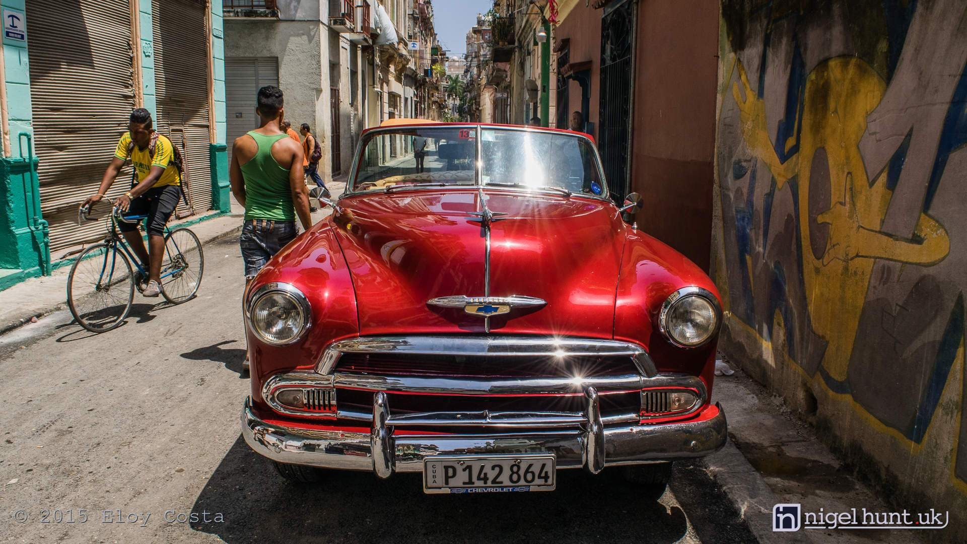 Cool 1951 convertible Chevrolet parked next to a street mural in Old Havana, Cuba