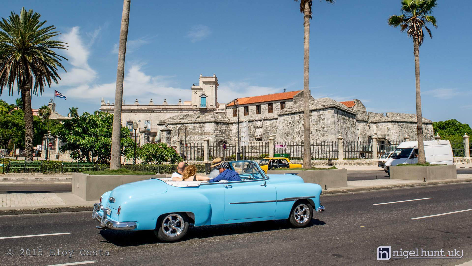 Tourists having a tour in vintage cars in the Malecon Avenue. In the background Castillo de la Real Fuerza